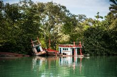 Ruin of sunken fishing boats in river. Thailand Stock Photos