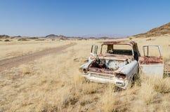 Ruina de la hierba seca media abandonada del coche clásico al lado del camino de tierra en Damaraland, Namibia, África meridional Fotos de archivo libres de regalías