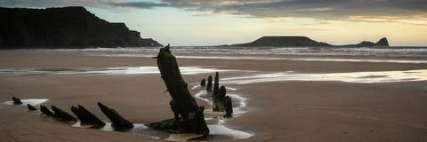 Ruina de la nave del panorama del paisaje en la playa de la bahía de Rhosilli en País de Gales en fotografía de archivo