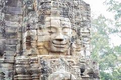 Ruina de piedra de la cara del templo budista antiguo Bayon en el complejo de Angkor Wat, Camboya Configuración antigua fotografía de archivo libre de regalías