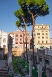 Ruinas antiguas de la columna rodeadas por las calles modernas en Roma, Italia Imagenes de archivo