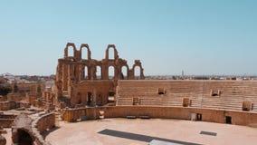 Ruinas antiguas del Amphitheatre del EL Jem con los asientos y el cielo azul almacen de metraje de vídeo