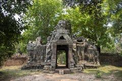 Ruinas antiguas del templo de Banteay Kdei en el complejo de Angkor Wat, Camboya La torre de piedra demolida con Buda hace frente foto de archivo libre de regalías
