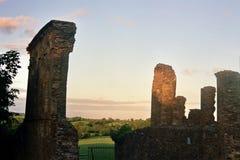 Ruinas antiguas en un paisaje irlandés de la puesta del sol Imagen de archivo libre de regalías