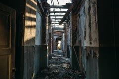 Ruinas de la casa del ladrillo quemado después del accidente del desastre del fuego Pasillo dentro, construyendo sin el tejado, m Imagen de archivo libre de regalías