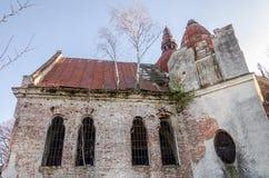 Ruinas de la iglesia de piedra vieja de las paredes arruinadas cuyo son los árboles Fotos de archivo libres de regalías