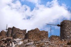 Ruinas de molinoes de viento antiguos en las montañas rocosas con el cielo azul con las nubes blancas imagen de archivo