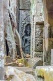 Ruinas de templos de Angkor Thom con las raíces de un spung y del devata ocultado detrás foto de archivo libre de regalías