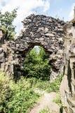 Ruinas del castillo con las rocas alrededor, camino y el cielo azul con las nubes Foto de archivo