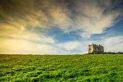 Ruinas viejas de una casa en un prado de la primavera en la puesta del sol Fotografía de archivo libre de regalías