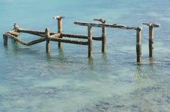 Ruinas viejas del puerto en el mar azul imagenes de archivo