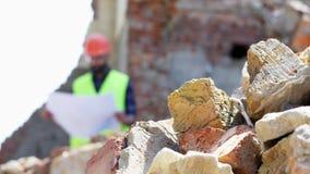 Ruinas y piedras en el primero plano En el constructor borroso del fondo que analiza el dibujo metrajes