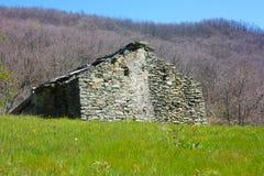 Ruine zerstört ein altes Haus errichtet von den Steinen verlassen in einer grünen Reinigung, mitten in der Beschaffenheit des Par lizenzfreie stockfotos