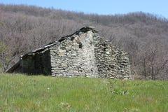 Ruine zerstört ein altes Haus errichtet von den Steinen verlassen in einer grünen Reinigung, mitten in der Beschaffenheit des Par lizenzfreie stockbilder