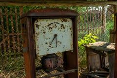Ruined abandonó el equipo viejo de la gasolinera durante verano en el pueblo olvidado perdido foto de archivo