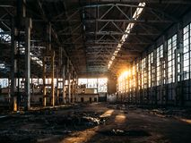 Ruined and abandoned dark creepy factory house building inside, industrial warehouse hall waiting for demolition. Toned stock image