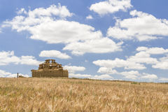 Ruined adobe pigeon house between a cereal field and a cloudy bl. Ruined adobe pigeon house between a barley field close to harvest and a cloudy blue sky in Stock Image