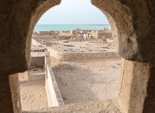 Abandoned mosque with minaret. Deserted village. A view out of minaret`s window to the sea. Al Jumail, Qatar. stock photo