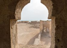 Ruined ancient Arab pearling, fishing town Al Jumail, Qatar. The desert at coast of Persian Gulf. View out of minaret window. stock images