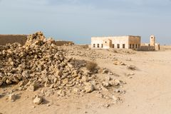 Ruined ancient old Arab pearling and fishing town Al Jumail, Qatar. The desert at coast of Persian Gulf. Pile of stones. royalty free stock image
