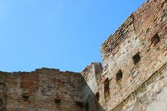 Old castle wall and sky. Ruined ancient tower with windows. Old destroyed castle on blue sky background stock image