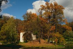 Ruined arc on island in park. Ruins of ancient arc on small island in autumn park Stock Photo