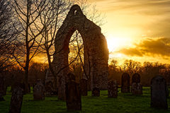 Ruined Arch at Sunset. The ruined arch in the graveyard of Wymondham Abbey in Norfolk, UK caught at sunset. There are many headstones in the foreground, trees to Stock Photos