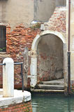 A ruined archway, Venice. A quiet canal beside a crumbling brick archway in Venice, Italy. The archway and nearby post are white, the bricks terracotta. the stock images