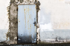Ruined brick wall closed steel door Stock Photo
