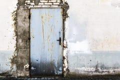 Ruined brick wall closed steel door Stock Photo