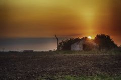 Ruined building with sunrise on the meadow. royalty free stock photography