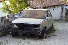 Ruined car next to paved road royalty free stock photo