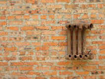 Ruined cast iron radiator for home on a brick wall. Royalty Free Stock Photo