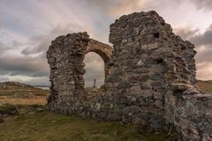 The ruined church and Saxon cross at Ynys Llanddwyn on Anglesey, North Wales stock image