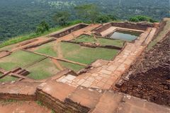 Ruined city on ancient Sigiriya rock with archeological area and pool, Sri Lanka. UNESCO world heritage site from 1982 Royalty Free Stock Image