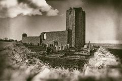 Ancient church ruins with small graveyard surrounded with stone wall in sepia royalty free stock image