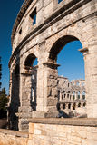 Ruined Colliseum in Pula, Croatia. Old ruined Colliseum in Pula, Croatia during the day with blue sky Stock Photo