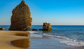 Ruined defense tower in the coastline shore. Ocean, beach and old ruined defense tower royalty free stock image