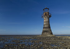 Ruined derelict lighthouse, space to top left. Whiteford Sands,. Whiteford Lighthouse is the only wave swept cast iron lighthouse in Britain. See here at low Royalty Free Stock Photo