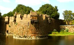 Giant battlement of vellore fort with trees and trench. A ruined fort battlement with trees at Vellore fort is a large 16th-century fort situated in the Vellore Stock Photography