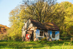 Ruined house. Heavily damaged and ruined house with autumn colored forest in background Royalty Free Stock Image