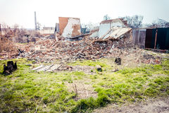 Ruined house. Old ruined house with green grass in the yard Royalty Free Stock Image