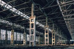 Ruined industrial hall of warehouse or hangar, creepy and old construction. Toned royalty free stock photo