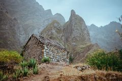 Ruined local storehouse nestled into incredible scenery with steep mountain rocks and vertical peaks. Trekkingtrail on. Santo Antao Cape Verde stock photography