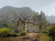 Ruined local storehouse nestled into incredible scenery with steep mountain rocks and vertical peaks. Trekkingtrail on. Santo Antao Cape Verde stock images