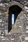 Ruined medievel castle arrow slot window. Arrow slot window in a castle ruins on the Isle of Islay in Scotland during the summer, with views of green fields and royalty free stock photos