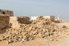 Ruined old Arab pearling and fishing town Al Jumail, Qatar. Pile of stones. The desert at coast of Persian Gulf. royalty free stock photo