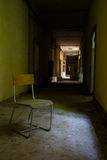 Ruined old hospital. An old chair in the middle of an aisle just in front of a window Stock Photography