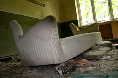 Ruined old hospital. A broken sofa of a waiting room in a ruined old hospital Royalty Free Stock Image