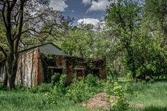Ruined old house in the forest. Ruined old creepy abandoned house located in the forest during summer time Royalty Free Stock Photo